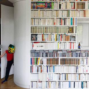 Exempel på ett mellanstort modernt allrum med öppen planlösning, med ett bibliotek, vita väggar och ljust trägolv