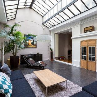 Cette image montre un grand salon design ouvert avec béton au sol, un mur beige, aucune cheminée et aucun téléviseur.