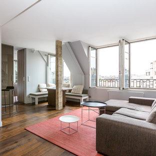 Aménagement d'un grand salon contemporain ouvert avec un mur gris, un sol en bois brun, aucune cheminée et aucun téléviseur.