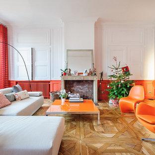 Imagen de salón para visitas cerrado, contemporáneo, grande, sin televisor, con parades naranjas, suelo de madera clara y chimenea tradicional