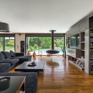 Cette image montre un salon design avec cheminée suspendue, un mur gris, un sol en bois brun, un manteau de cheminée en métal, un téléviseur encastré et un sol marron.