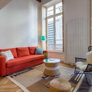 Cette image montre un salon design avec un mur blanc et un sol en bois clair.