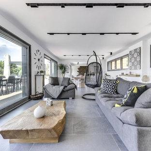 Exemple d'un salon tendance ouvert avec un mur blanc et un sol gris.