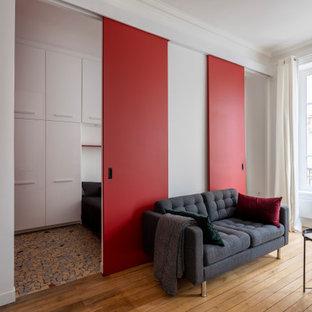 Modelo de salón abierto y boiserie, moderno, pequeño, boiserie, con paredes rojas, suelo de madera clara, chimenea tradicional, marco de chimenea de madera, televisor retractable, suelo beige y boiserie