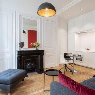 Foto de salón abierto y boiserie, minimalista, pequeño, boiserie, con paredes rojas, suelo de madera clara, chimenea tradicional, marco de chimenea de madera, televisor retractable, suelo beige y boiserie
