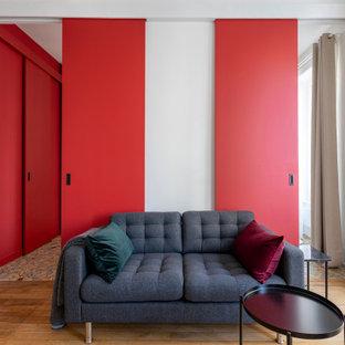 Diseño de salón abierto y boiserie, contemporáneo, pequeño, boiserie, con paredes rojas, suelo de madera clara, chimenea tradicional, marco de chimenea de madera, televisor retractable, suelo beige y boiserie