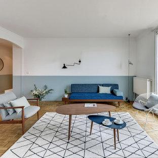 Réalisation d'un grand salon nordique ouvert avec un sol en bois clair, aucune cheminée, aucun téléviseur et un mur multicolore.