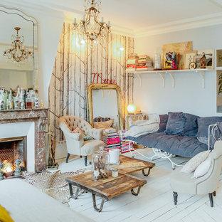 Idée de décoration pour un salon bohème de taille moyenne et fermé avec une salle de réception, un mur gris, un sol en bois peint, une cheminée standard, un manteau de cheminée en pierre et aucun téléviseur.