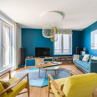 Idée de décoration pour un salon vintage avec un mur bleu, un sol en bois brun, un téléviseur indépendant et un sol marron.