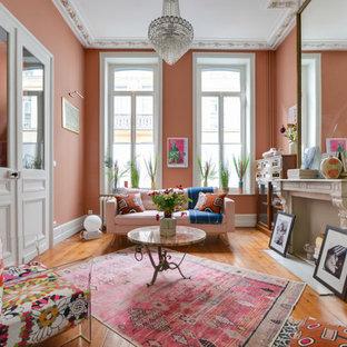 Cette photo montre un salon éclectique avec une salle de réception, un mur rose, un sol en bois brun, une cheminée standard, aucun téléviseur et un sol marron.