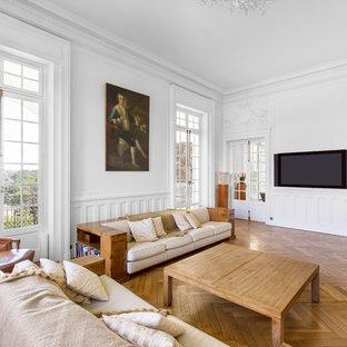 Aménagement d'un salon classique avec un mur blanc, un sol en bois brun, un téléviseur fixé au mur et un sol marron.