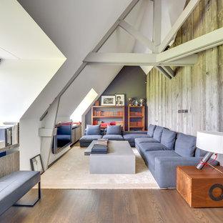 Aménagement d'un grand salon avec une bibliothèque ou un coin lecture contemporain avec un mur blanc, un téléviseur fixé au mur, aucune cheminée et un sol en bois brun.