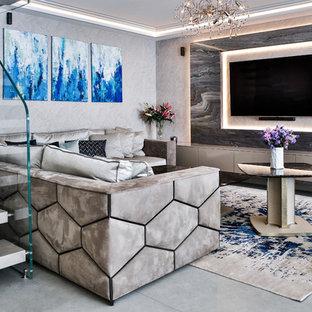 Réalisation d'un salon design avec un mur gris, un téléviseur fixé au mur et un sol gris.