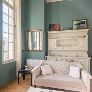 Cette image montre un salon traditionnel avec un mur vert, un sol en bois brun, aucune cheminée et aucun téléviseur.