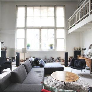 パリの中サイズのインダストリアルスタイルのおしゃれなLDK (白い壁、淡色無垢フローリング、標準型暖炉、コンクリートの暖炉まわり、テレビなし、グレーの床) の写真