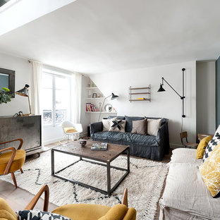 This is an example of a large industrial living room in Paris with a reading nook, blue walls, light hardwood flooring, no fireplace and no tv.