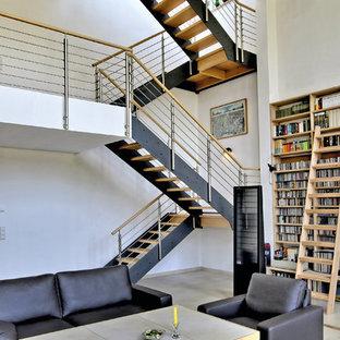 Aménagement d'un grand salon industriel ouvert avec un mur blanc et béton au sol.