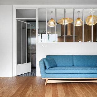 Cette image montre un salon nordique de taille moyenne et ouvert avec un mur blanc, un sol en bois brun et aucune cheminée.