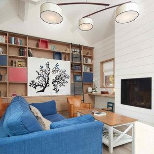Exemple d'un salon bord de mer de taille moyenne et ouvert avec un mur blanc, un sol en bois brun, une cheminée standard, un téléviseur dissimulé et un sol marron.
