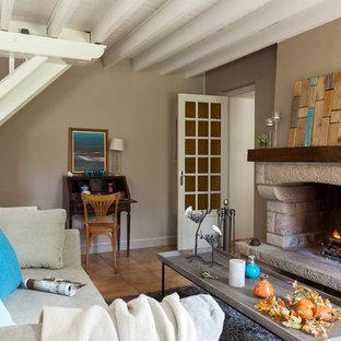 Aménagement d'un petit salon campagne fermé avec un mur marron, une cheminée standard, un manteau de cheminée en pierre et aucun téléviseur.