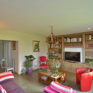 Foto di un soggiorno tradizionale con libreria, pareti beige, pavimento in legno verniciato e TV nascosta