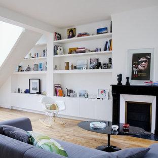 Cette photo montre un salon tendance avec un mur blanc, un sol en bois brun, une cheminée standard et un sol marron.