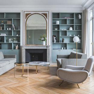 Inspiration pour un salon design ouvert avec un mur gris, un sol en bois clair, une cheminée standard, un manteau de cheminée en brique et un sol beige.