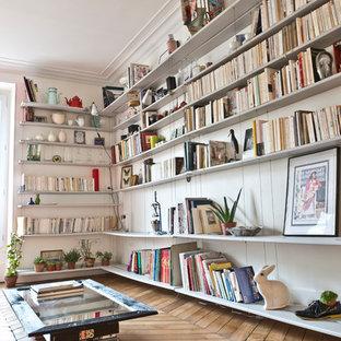Réalisation d'un salon avec une bibliothèque ou un coin lecture design de taille moyenne et ouvert avec un mur blanc, un sol en bois brun, aucune cheminée et aucun téléviseur.
