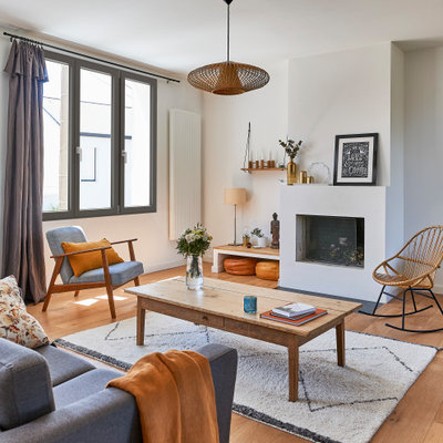 Mid-sized danish medium tone wood floor and beige floor living room photo in Paris with white walls, a standard fireplace and a plaster fireplace