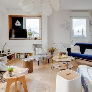 Cette photo montre un salon éclectique de taille moyenne et ouvert avec un mur blanc, un sol en bois clair, aucune cheminée, un téléviseur indépendant et un sol beige.