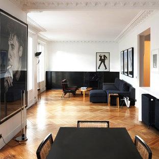 Cette photo montre un grand salon tendance ouvert et haussmannien avec un mur blanc, un sol en bois brun, aucune cheminée et aucun téléviseur.