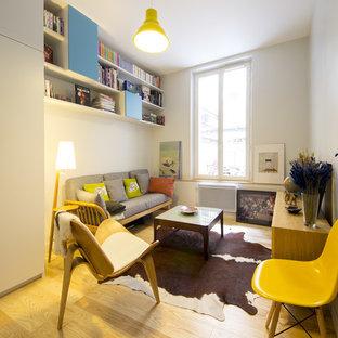 Idée de décoration pour un salon avec une bibliothèque ou un coin lecture nordique de taille moyenne et fermé avec un sol en bois clair, un mur blanc, aucune cheminée et aucun téléviseur.