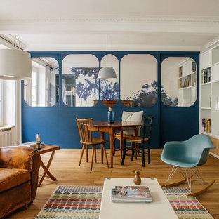 Idée de décoration pour un salon design de taille moyenne et ouvert avec un mur blanc, un sol en bois clair, une cheminée standard, un manteau de cheminée en pierre, un téléviseur fixé au mur, une salle de réception et un sol beige.