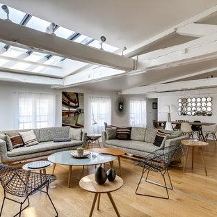 Réalisation d'un grand salon bohème ouvert avec un mur blanc, un sol en bois clair, une salle de réception, aucune cheminée et aucun téléviseur.