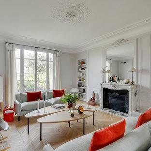 Idées déco pour un grand salon classique fermé avec un mur blanc, un sol en bois clair, une cheminée standard, aucun téléviseur, une salle de réception et un manteau de cheminée en pierre.
