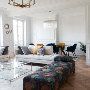 Idée de décoration pour un grand salon tradition ouvert avec un mur blanc, un sol en bois clair, un sol beige et boiseries.