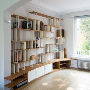 Ejemplo de biblioteca en casa abierta, actual, grande, sin televisor, con paredes blancas y suelo de madera clara