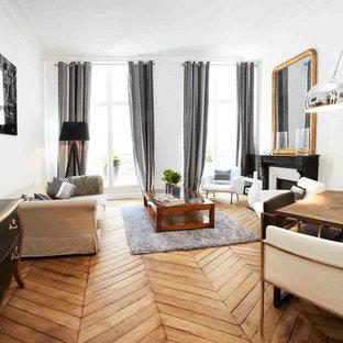 Cette photo montre un grand salon éclectique ouvert avec une salle de réception, un mur blanc, un sol en bois brun, une cheminée standard, un manteau de cheminée en pierre et aucun téléviseur.