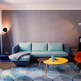 Cette photo montre un salon avec une bibliothèque ou un coin lecture tendance de taille moyenne et ouvert avec aucune cheminée, aucun téléviseur, un mur gris et un sol en bois foncé.