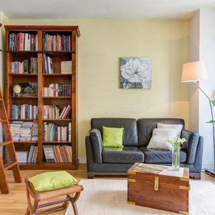 Cette image montre un salon avec une bibliothèque ou un coin lecture traditionnel de taille moyenne et fermé avec un mur jaune, un sol en bois clair, aucune cheminée et aucun téléviseur.