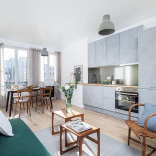 Cette image montre un salon nordique ouvert avec un mur blanc, un sol en bois clair et un sol beige.
