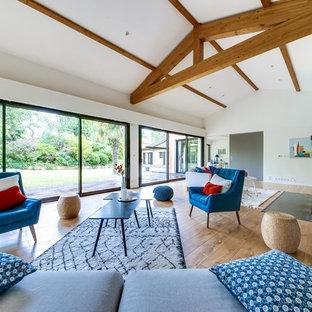 Aménagement d'un très grand salon contemporain ouvert avec un mur blanc, un sol en bois clair, une cheminée standard, un manteau de cheminée en brique, une salle de réception et un sol beige.