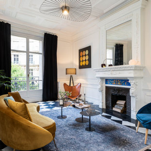 Cette photo montre un salon tendance fermé avec un mur blanc, une cheminée standard et du lambris.