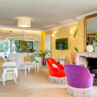 Idées déco pour un salon éclectique avec un mur jaune, une cheminée standard et un téléviseur fixé au mur.