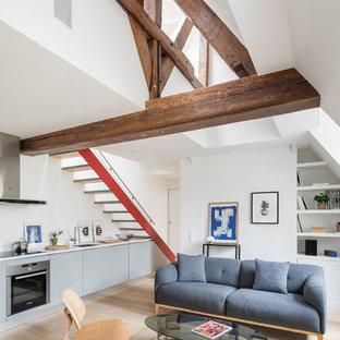 Idée de décoration pour un salon design ouvert avec un mur blanc, un sol en bois clair et un sol beige.