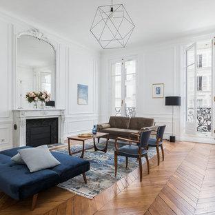 Cette photo montre un salon chic avec une salle de réception, un mur blanc, un sol en bois brun, une cheminée standard et aucun téléviseur.