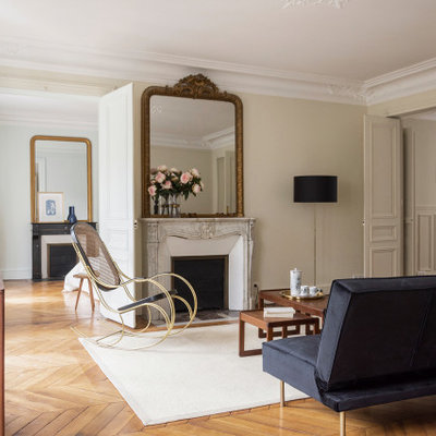 Example of a transitional medium tone wood floor and brown floor living room design in Paris with beige walls and a standard fireplace