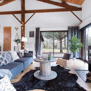 Idées déco pour un grand salon éclectique ouvert avec un mur blanc, un sol en bois clair, un poêle à bois et aucun téléviseur.
