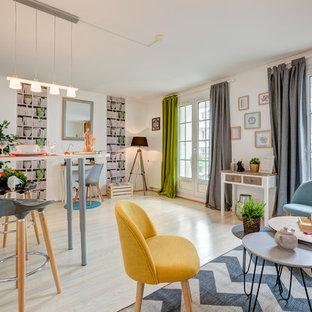 Aménagement d'un salon éclectique ouvert avec un mur blanc, un sol en bois clair et un sol beige.
