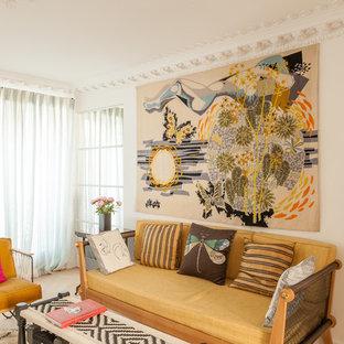 Idée de décoration pour un salon bohème avec un mur blanc, un sol en bois clair et un sol beige.